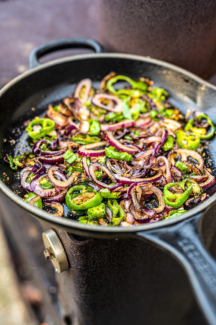Cooked jalapenos and onion rings in a cast iron pan
