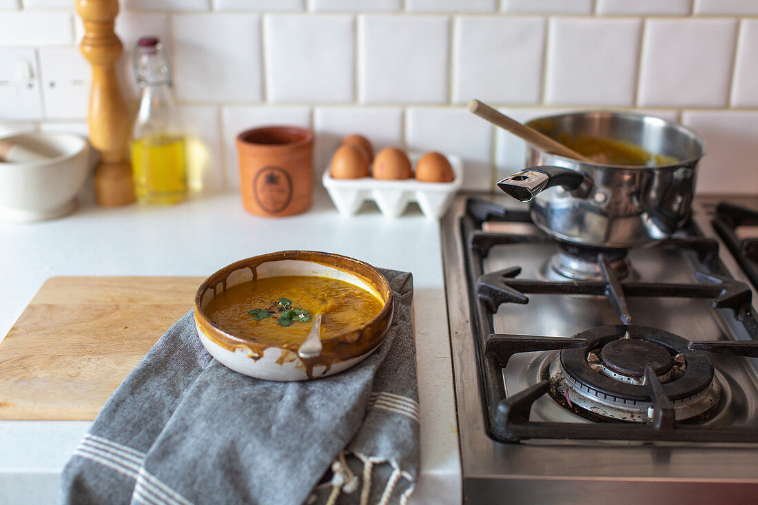 Cream soup in a ceramic bowl next to a gas stove in a country kitchen