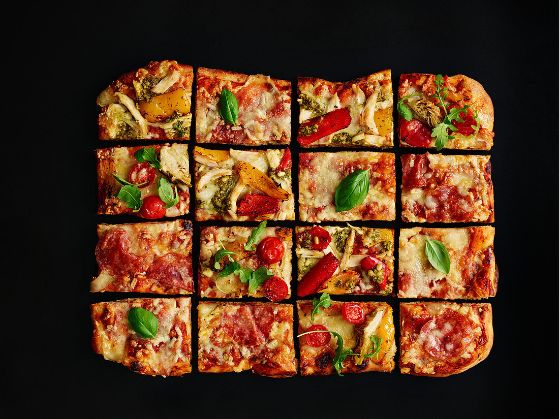 Colorful salami pizza baked in a tray, sliced