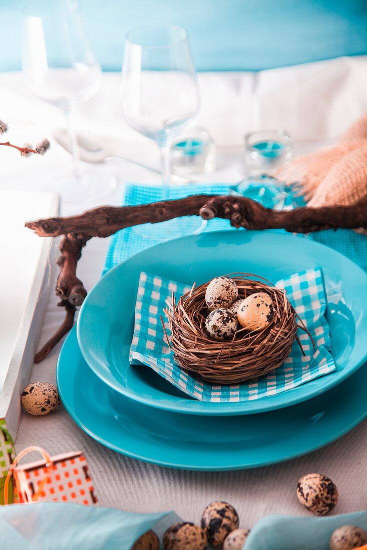 Blaues Tischgedeck österlich dekoriert mit Wachteleiern in Osternest