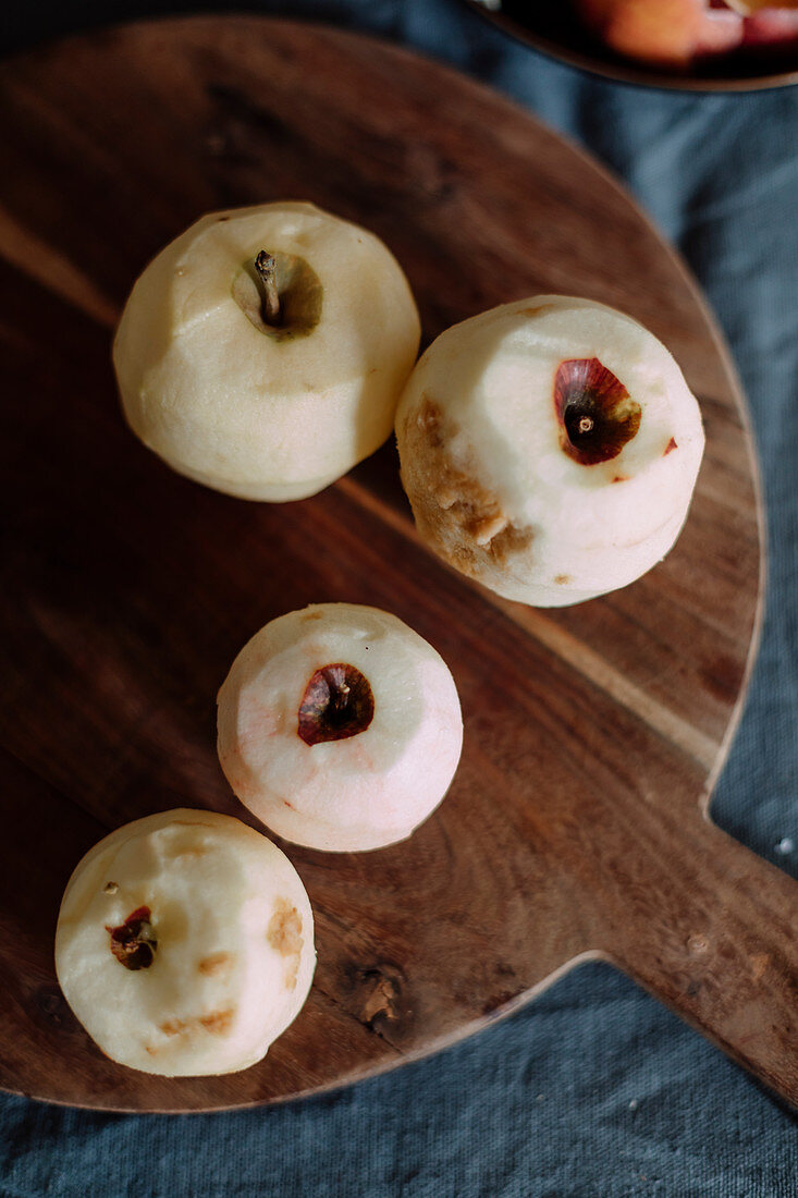 Peeled organic apples on a wooden board