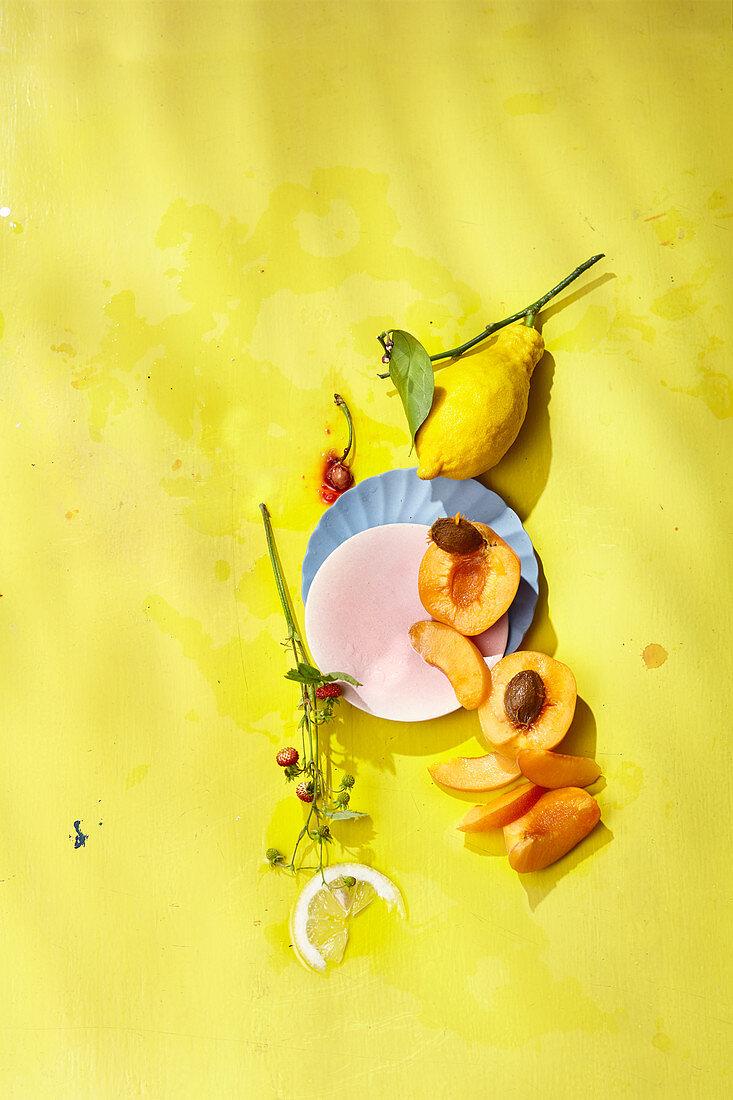 Zitronen und Aprikosen auf gelbem Untergrund