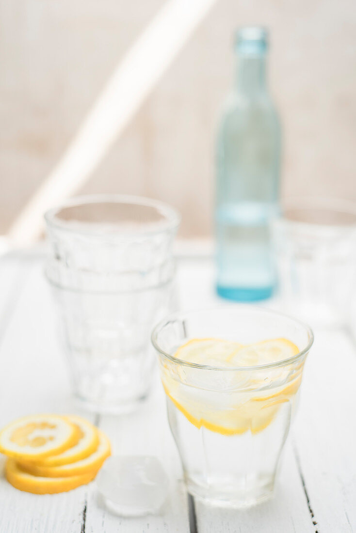 Fresh water in a glass with ice cubes and lemon slices