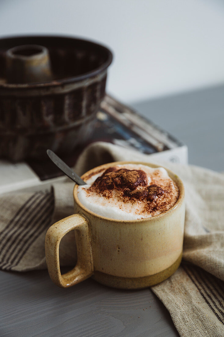 Cappuccino with milk foam and cocoa powder in a ceramic cup