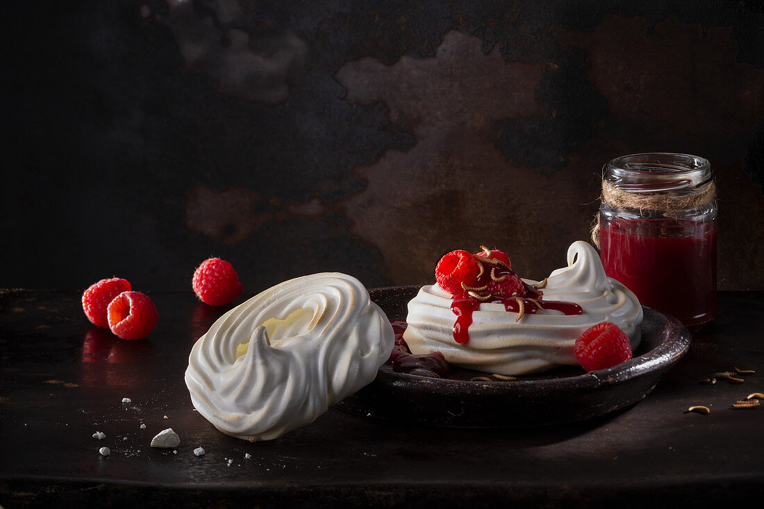 Meringue with raspberry sauce and buffalo worms