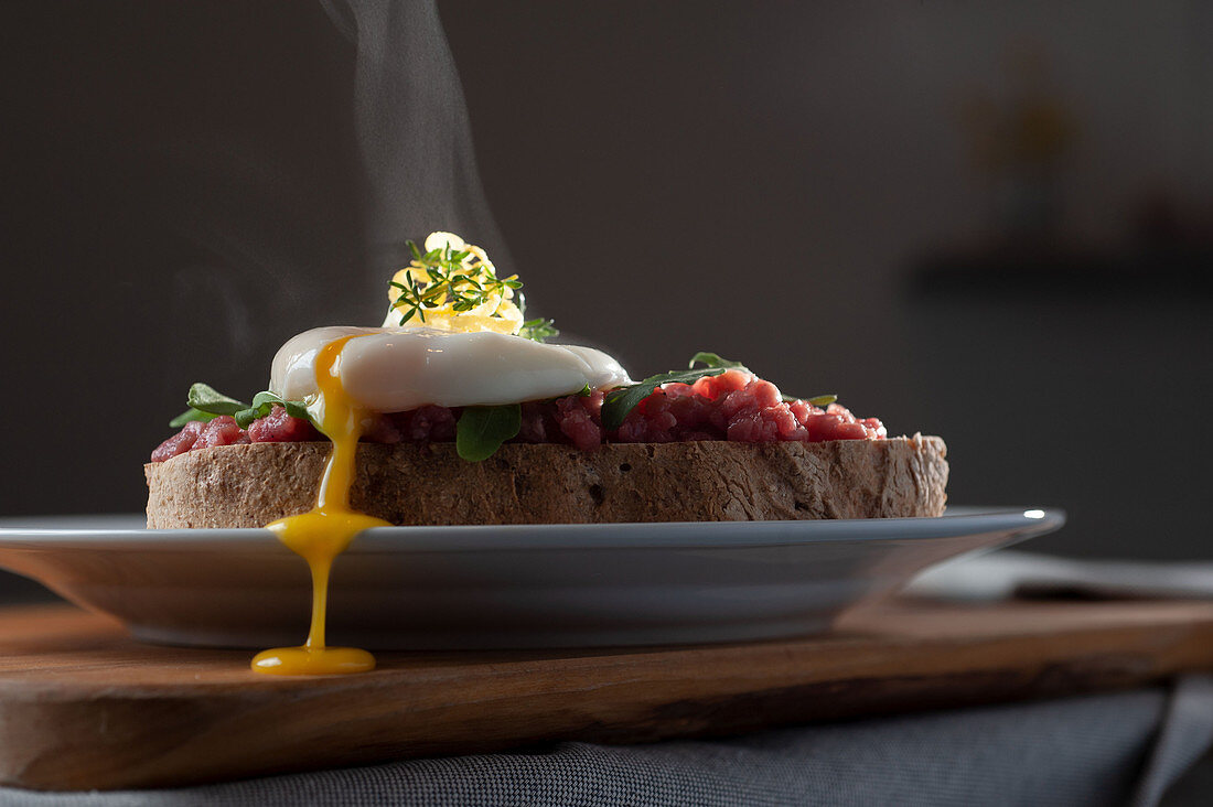 Poached egg on beef tartare and bread