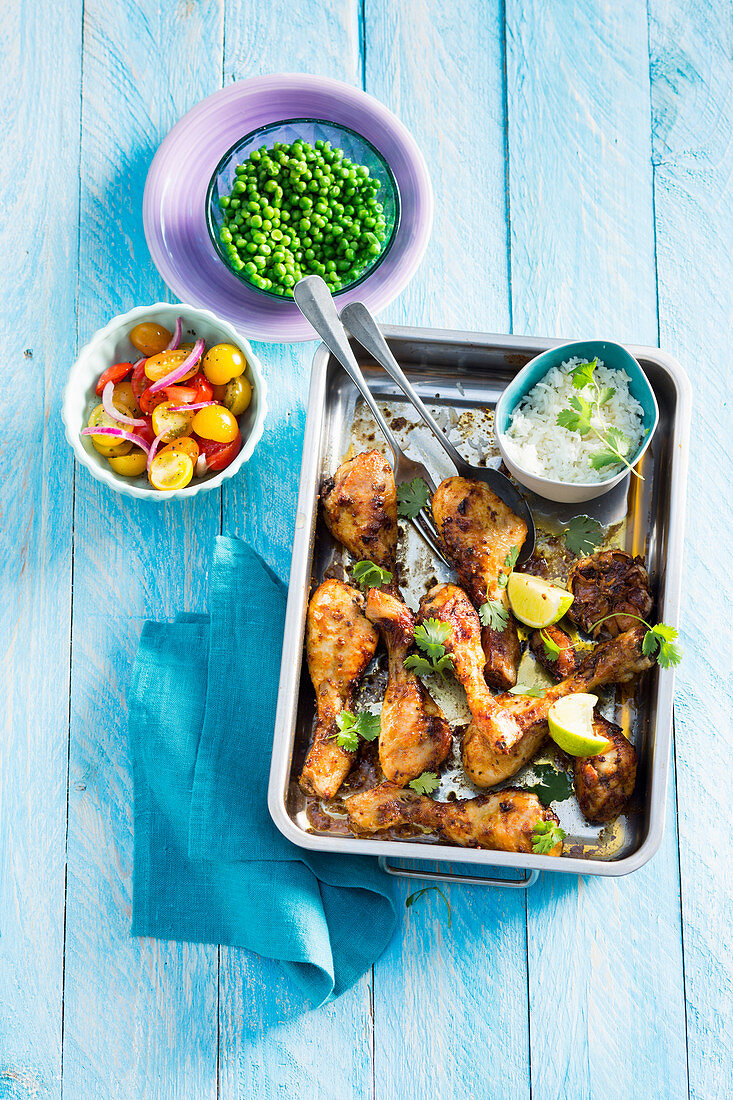 Tray bake chicken legs with rice, peas and tomato salad