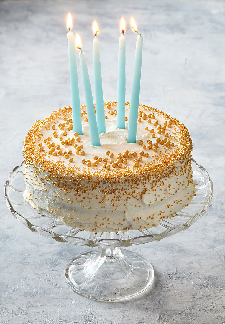 Birthday cake scented with black tea and decorated with golden sugar pearls