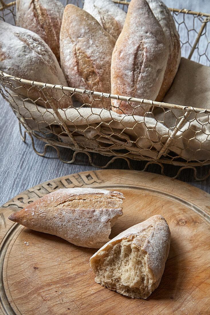 Sourdough bread rolls spilling out of a basket