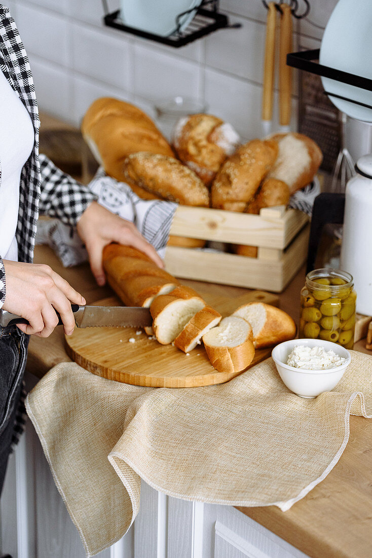Woman in the kitchen makes sandwiches from baguette and cream cheese