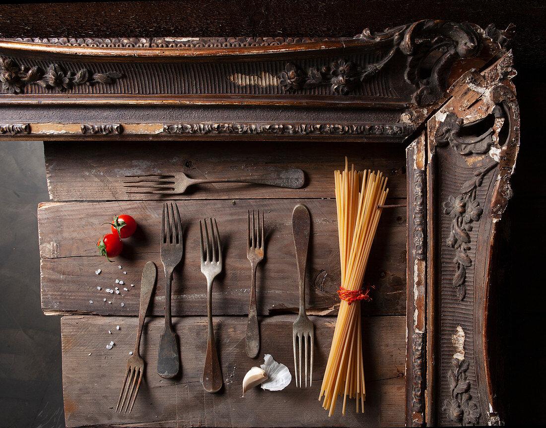 Stillleben mit antiken Gabeln, Spaghetti, Knoblauch und Tomaten in Holzrahmen