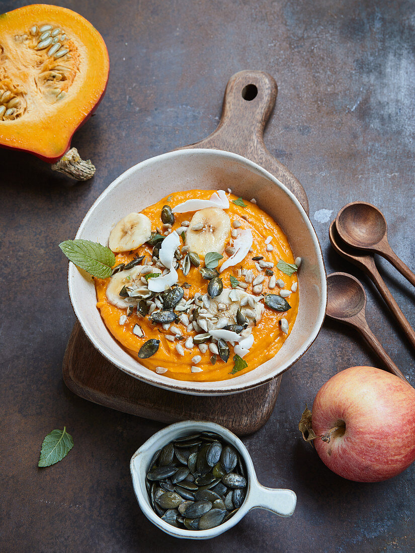 Pumpkin smoothie bowl with apple, coconut chips and ginger