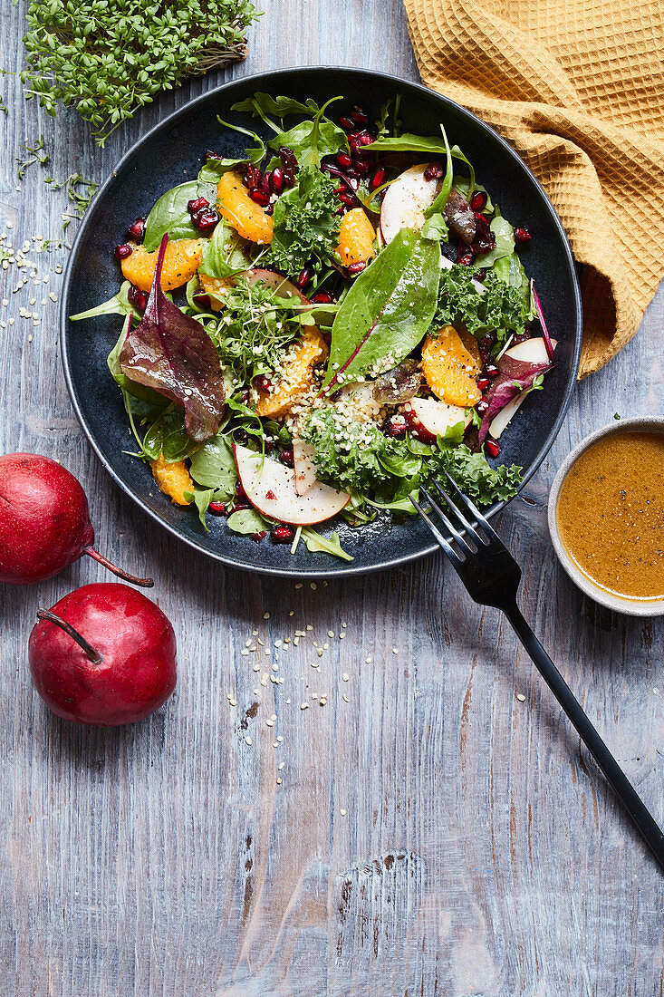 Winter salad with pomegranate seeds, pears and hemp seeds