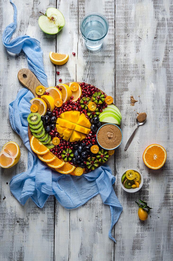 Fresh winter fruit platter with mango, oranges, kiwi, kumkquat, grapefruit and almond butter