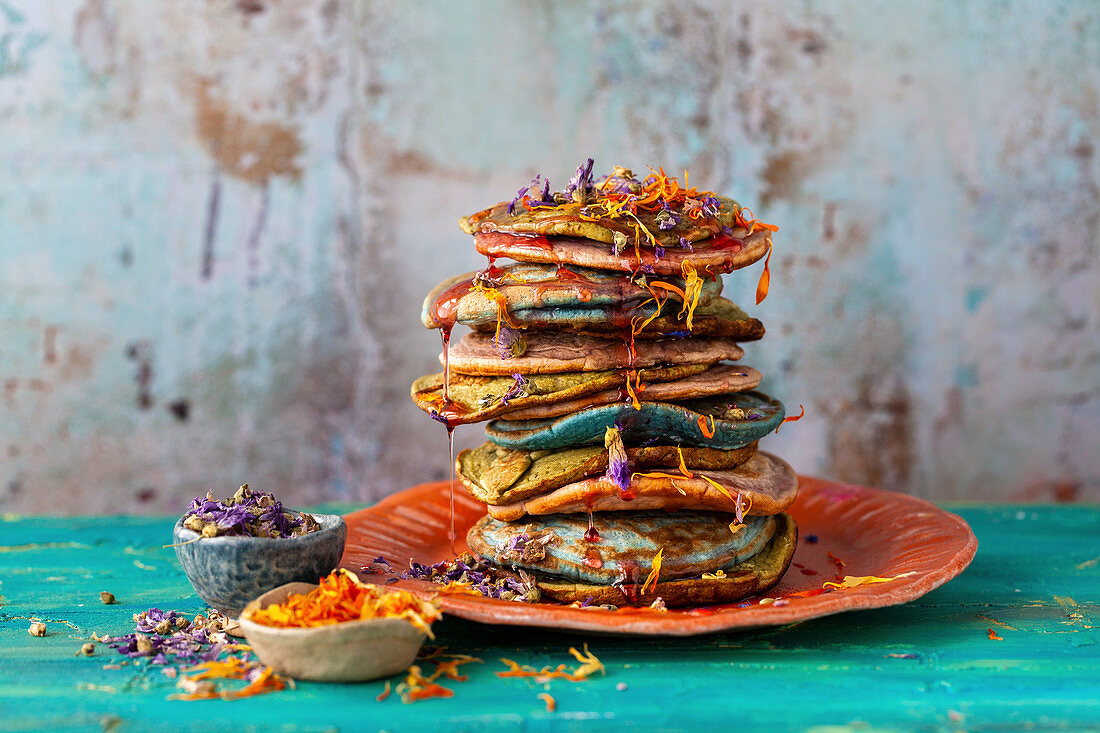 Naturally coloured pancakes served with edible flowers and syrup