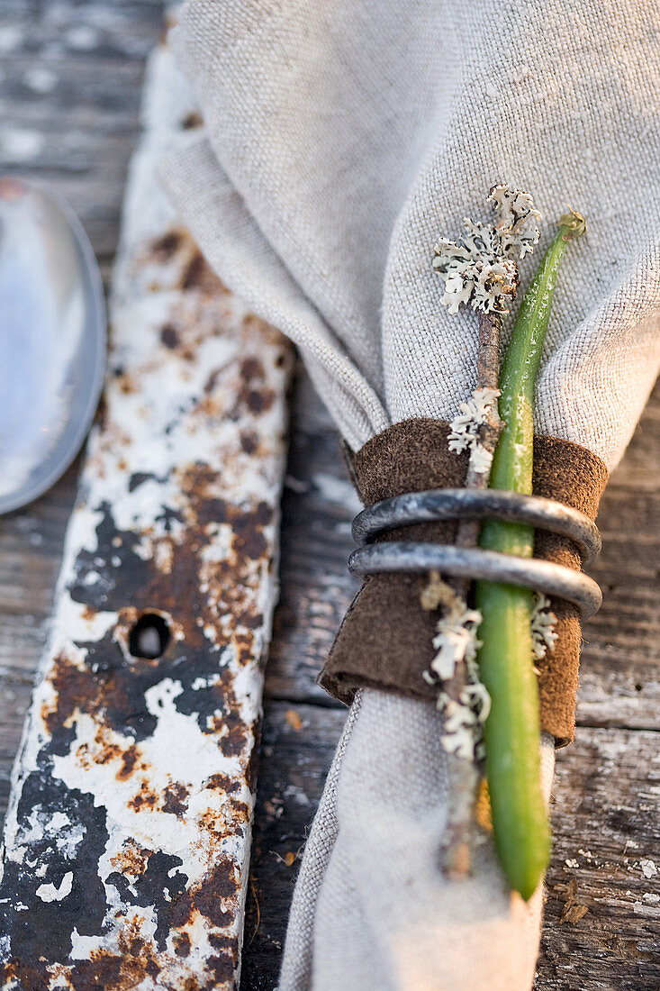 Linen napkin decorated with suede, iron rings, bean, and twig