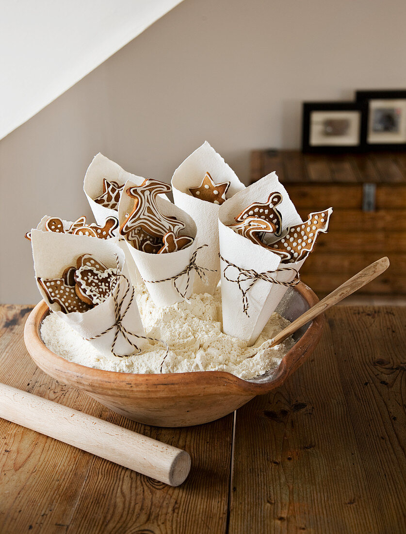 Paper cones of decorated gingerbread biscuits in bowl