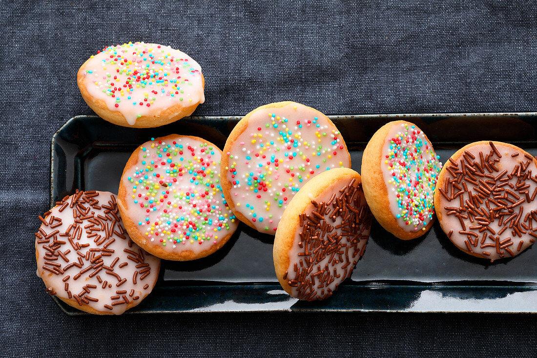 Mini Amerikaner (soft, sponge cake-like shortbread) with sugar sprinkles