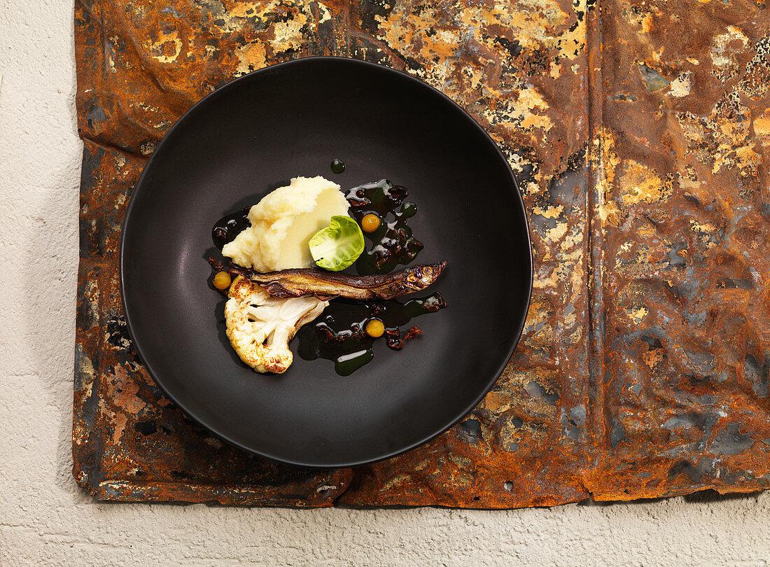 Sardelle mit Öl beträufelt serviert mit Blumenkohl und Kartoffelpüree