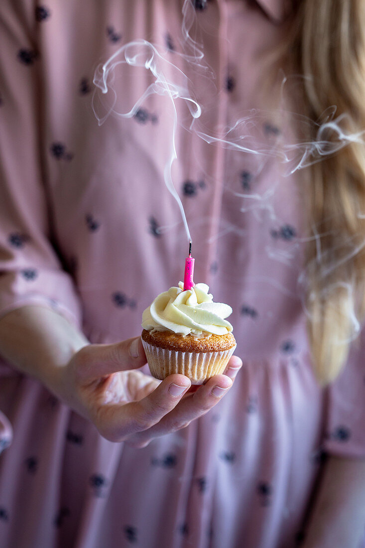 Woman in a pink dress holding a cupcake with a pink candle and smoke coming out from it