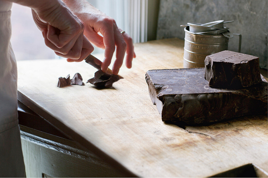 Hands Cutting Chunks of Dark Chocolate