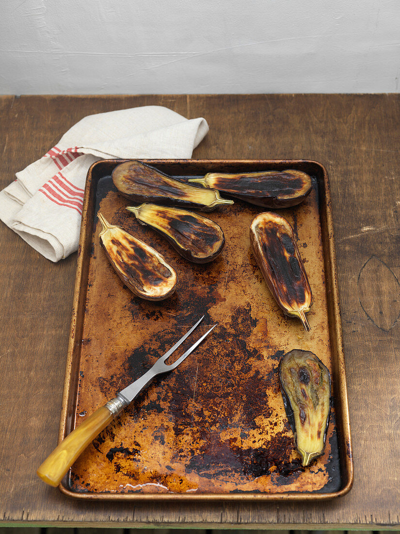 Roasted Eggplant on Baking Tray With Tea Towel and Two-Tine Fork
