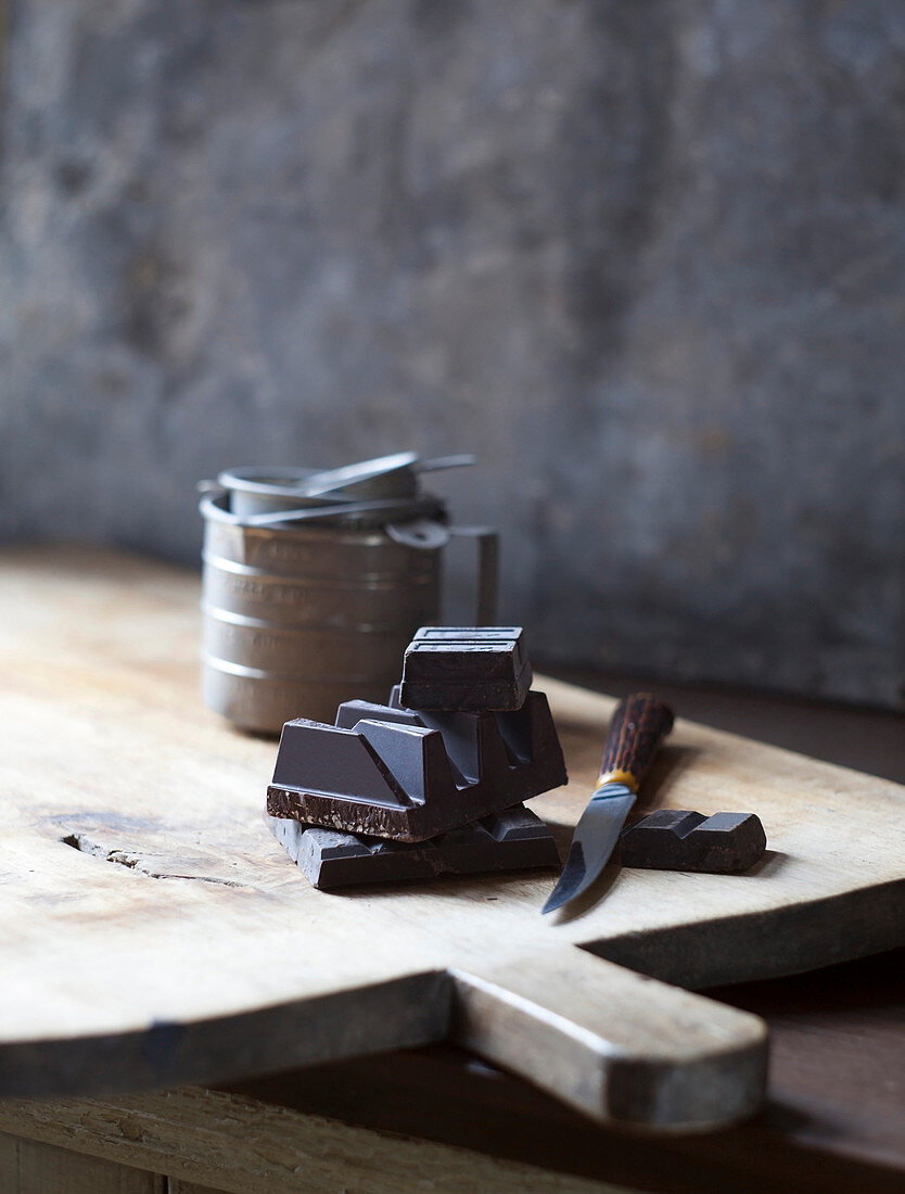 Chunks of Chocolate on Wooden Cutting Board with Knife and Tin Measuring Cups
