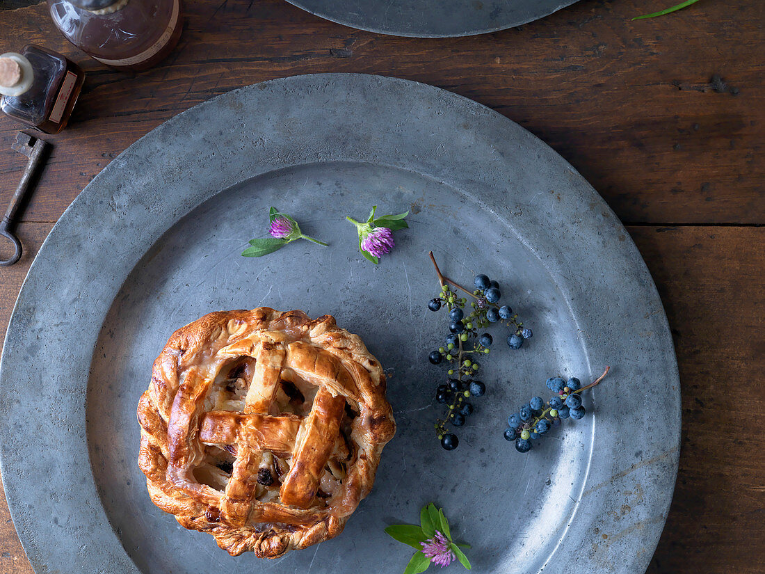 Pewter Plate with Small Rustic Pie on Wooden Surface with Old Key, Bottles, Clover and Berries