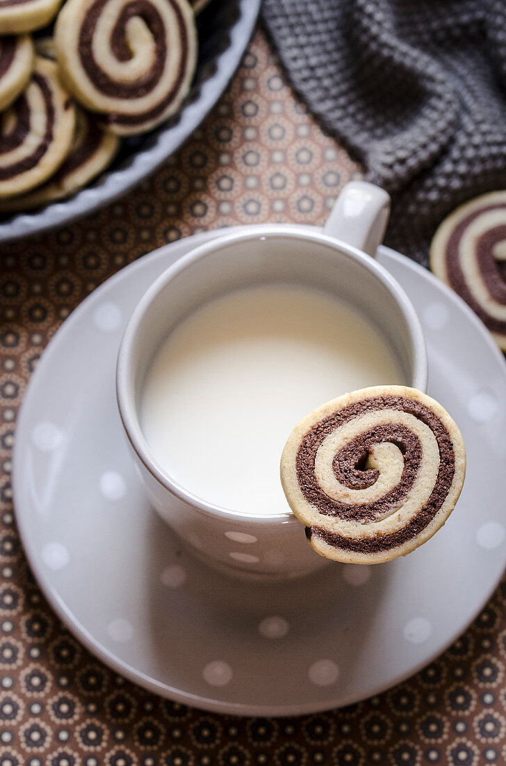 Black and white swirl cookie on cup of milk