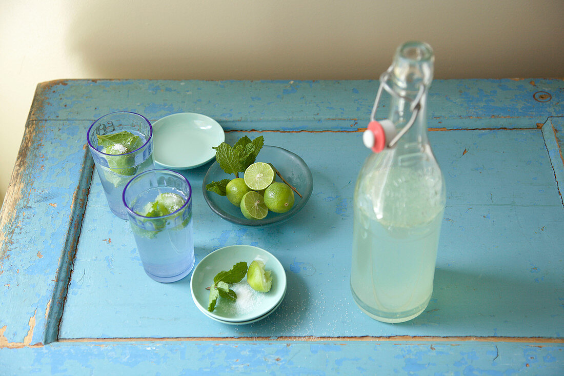 Mojito cocktails in blue drinking glasses with open bottle and bowls of limes, mint and sugar