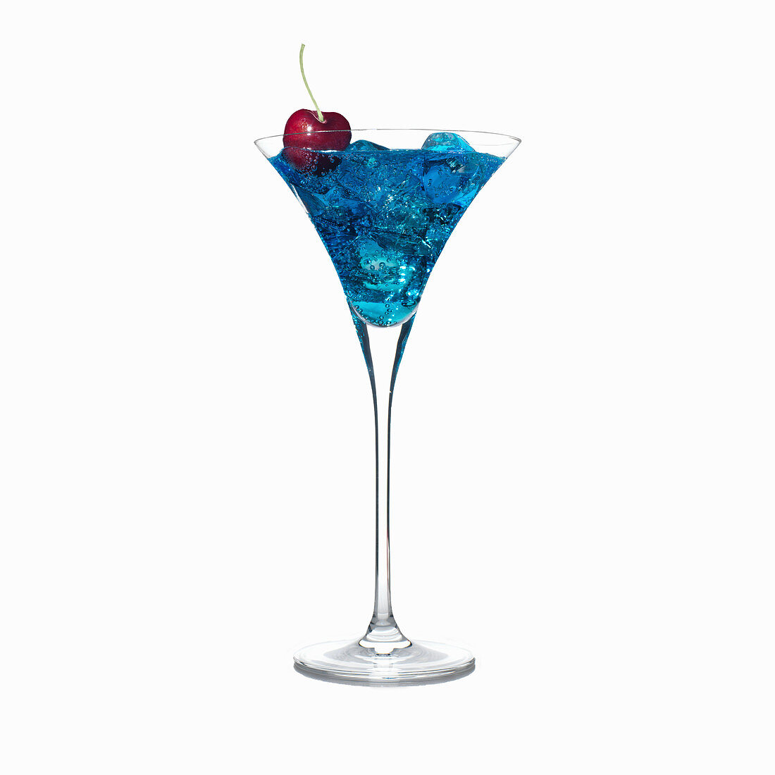 Blue cocktail in martini glass with ice cubes and a cherry garnish