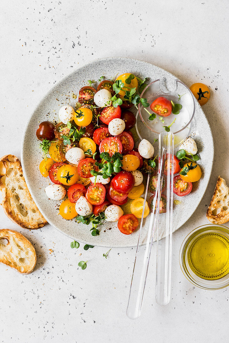 Cherry tomato and mozzarella salad with japanese white radish and cress micro greens