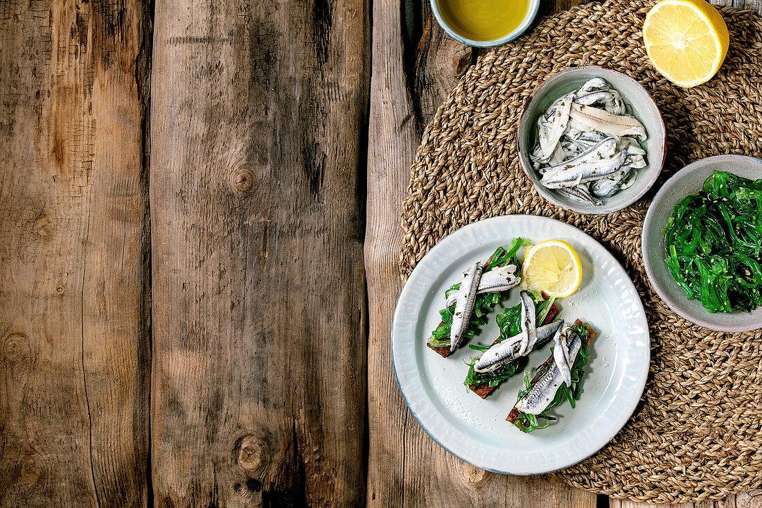 Pickled sardines in oil with lemon and rye bread, Wakame seaweed salad