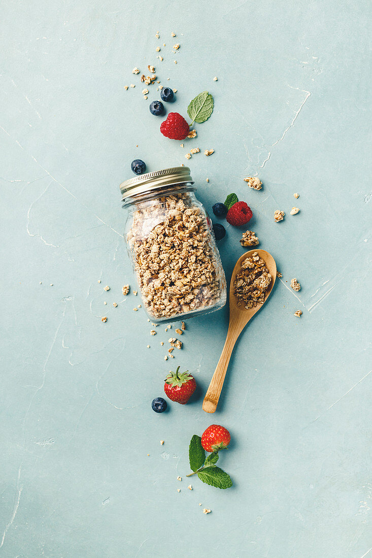 Homemade granola in a glass jar with berries