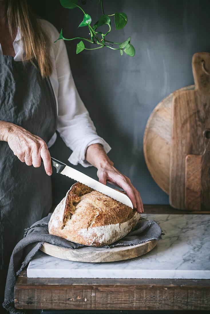Woman cuts homemade sourdough bread