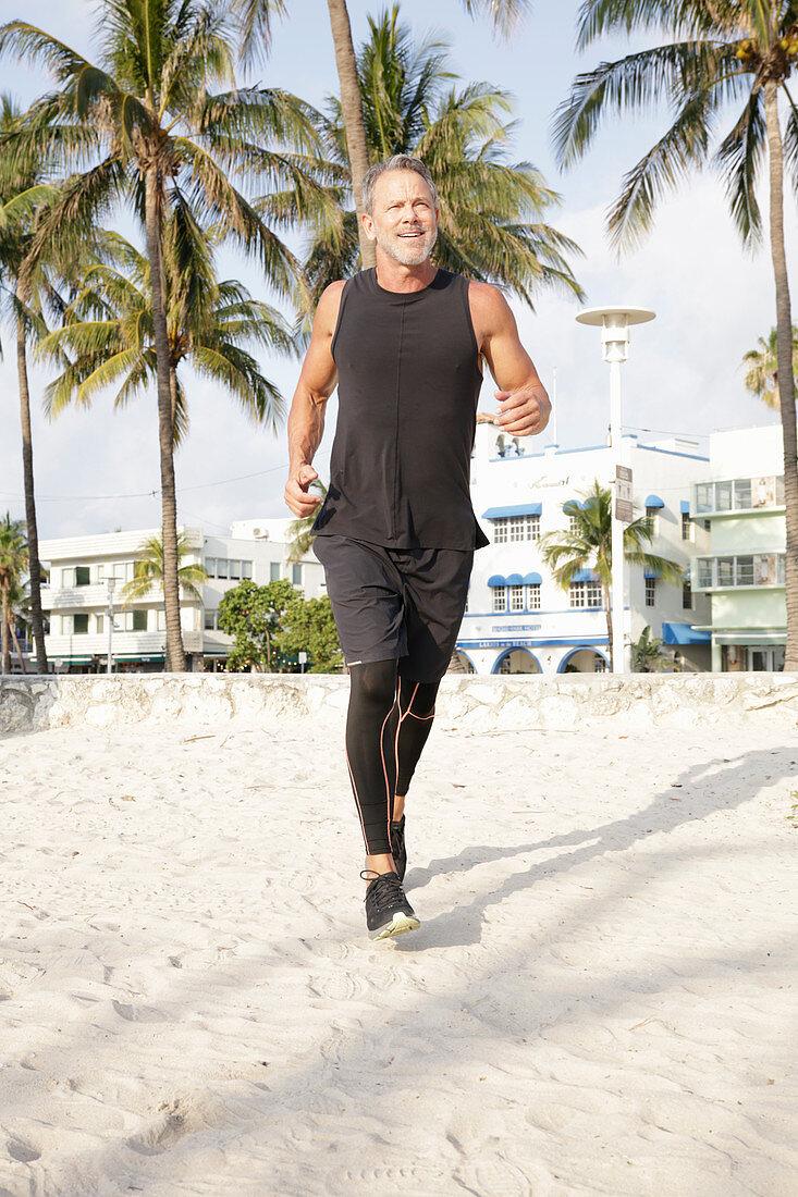 Grauhaariger Mann in schwarzer Sportbekleidung beim Joggen