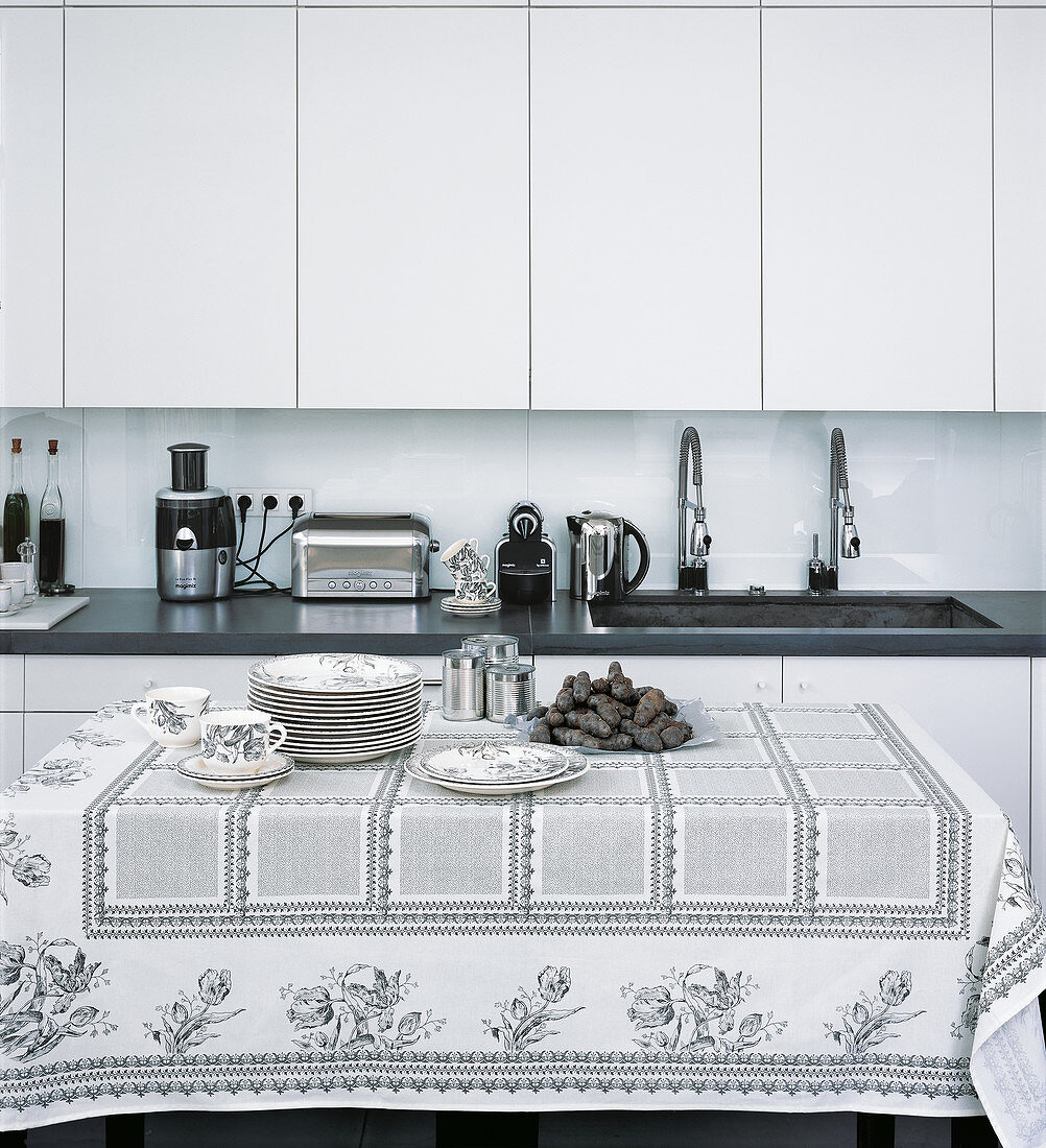 Black and white modern kitchen with plates and black potatoes on table