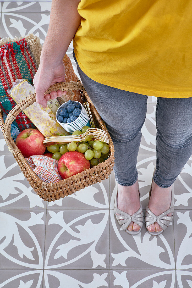 Woman holding a picnic basket with fruit and nougat bread