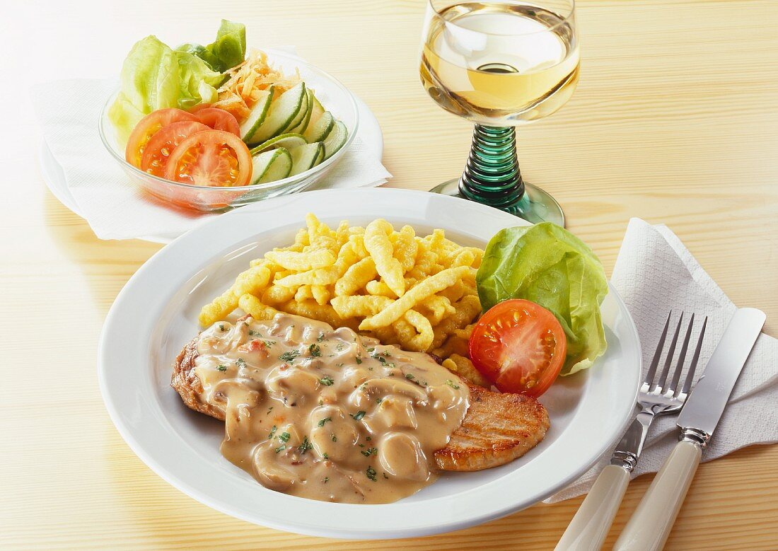 Escalope with mushroom cream sauce, noodles & bowl of lettuce