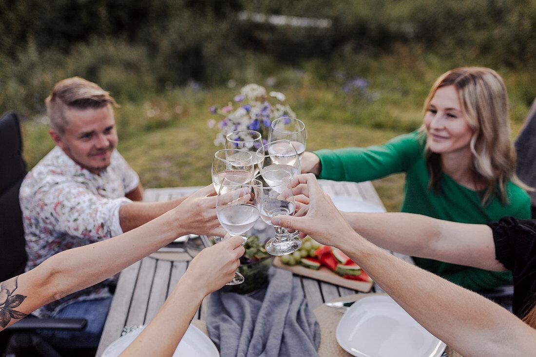 Friends raising glasses during garden party