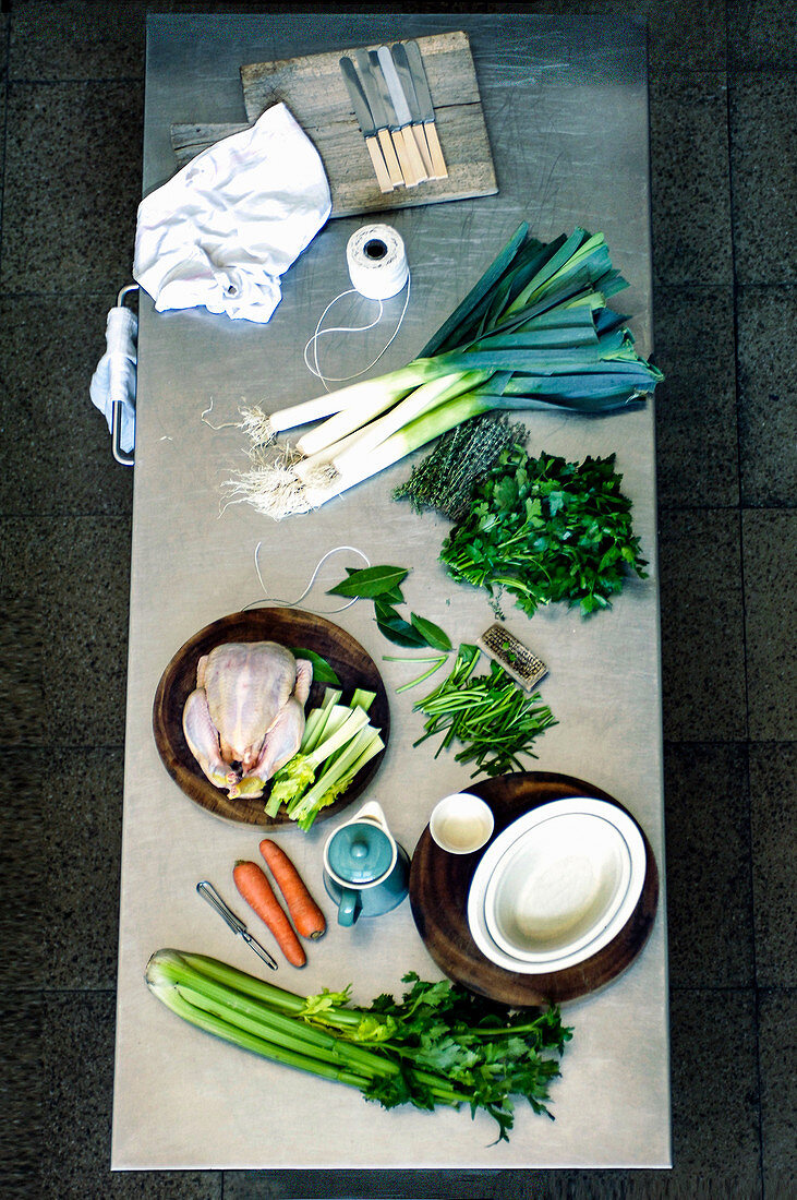 Kitchen table with leeks, carrots, celery, herbs and a chicken being prepared for a casserole