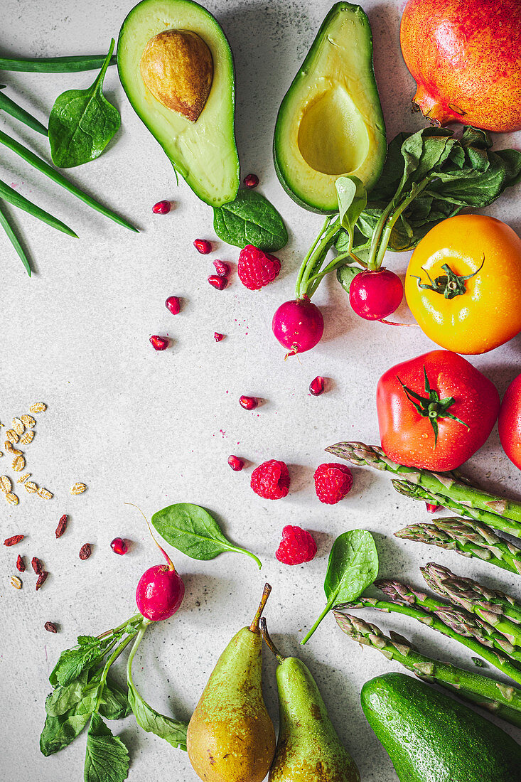 Colorful fruits and vegetables - avocado, asparagus, chives, tomatoes, radishes, spinach, pomegranate, raspberries, oatmeal, seeds