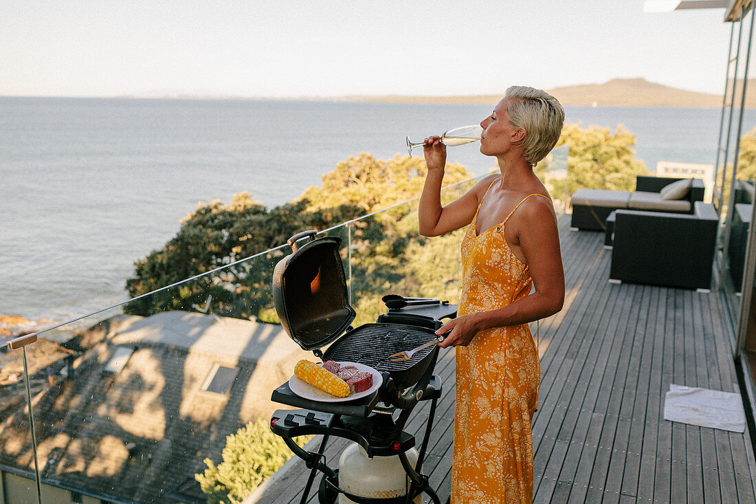 Woman drinking champagne near barbecue