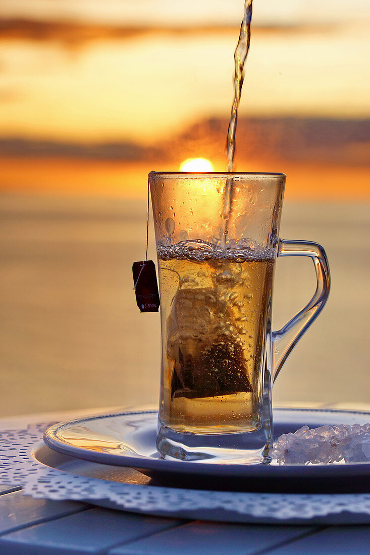 Hot tea with tea bags in a glass, by the sea before sunset