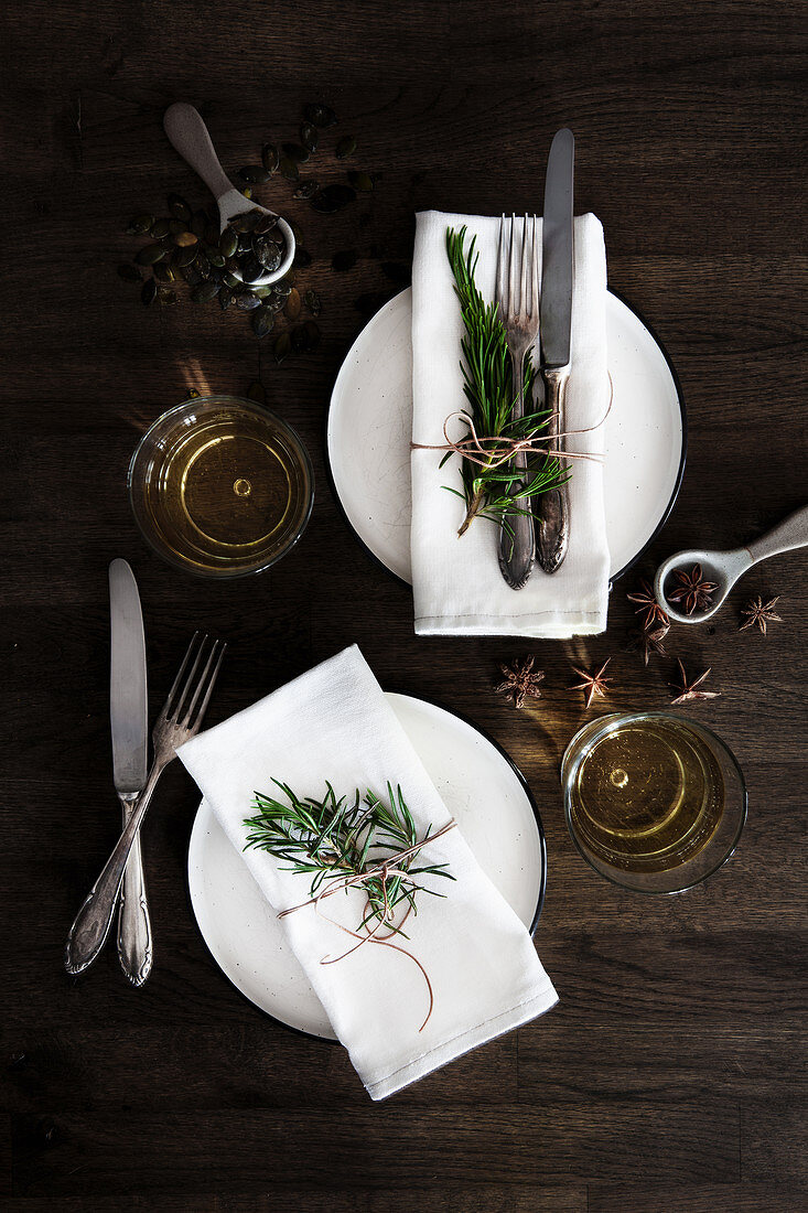 Place settings with napkins, cutlery, herbs, and spices