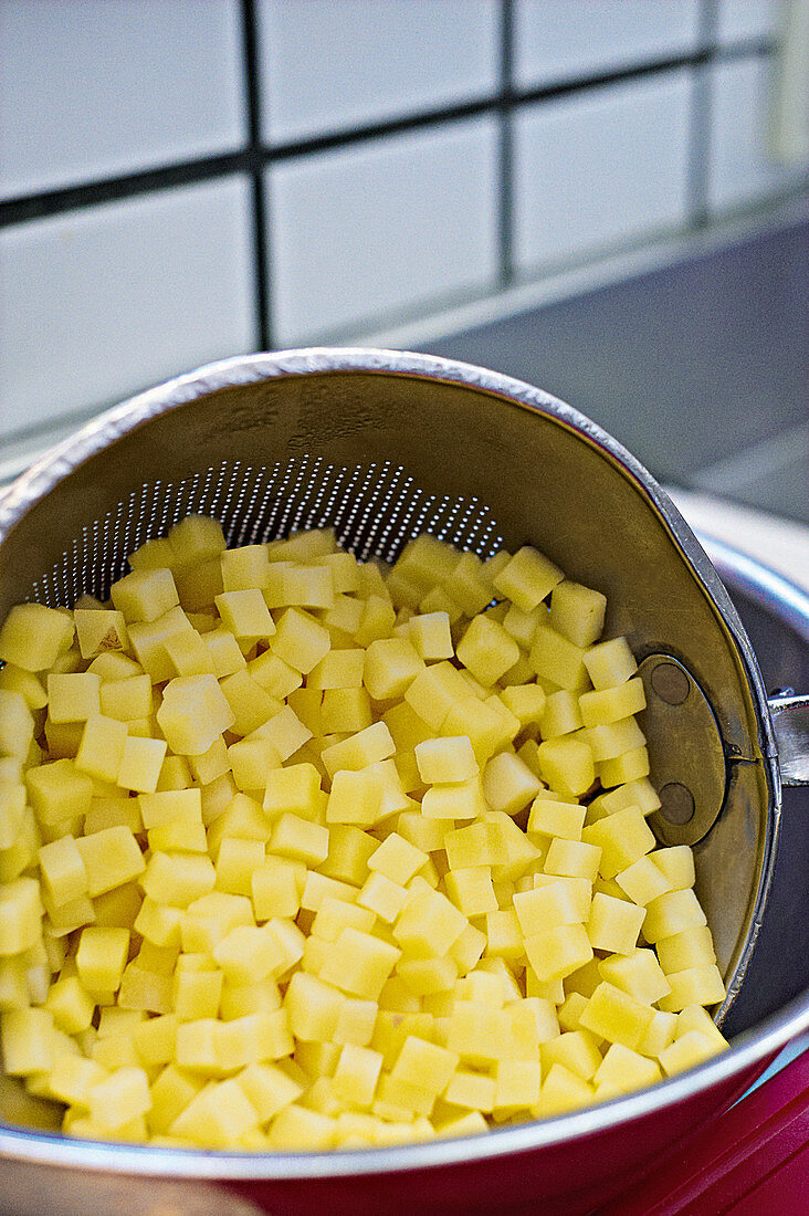 Draining washed, diced potatoes