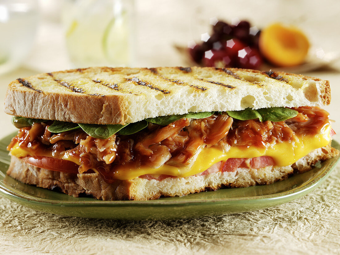 BBQ chicken and cheese pannini with tomato and spinach