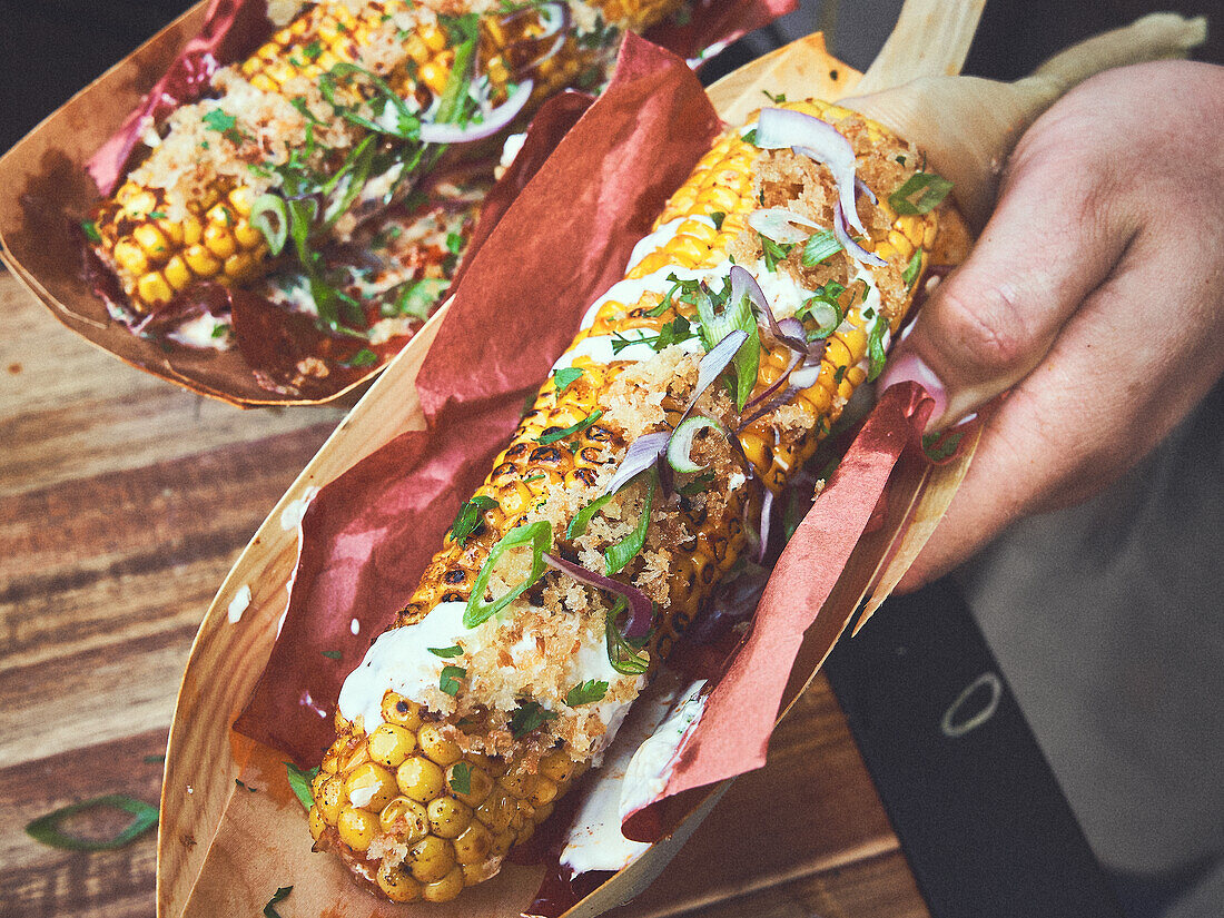 Grilled corn on the cob with sour cream and spices
