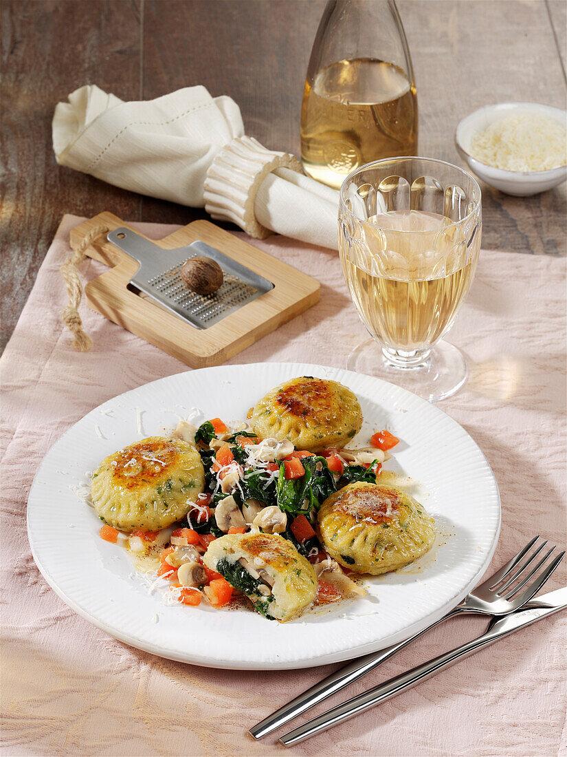 Potato Maultaschen (Swabian ravioli) with a spinach and mushroom medley