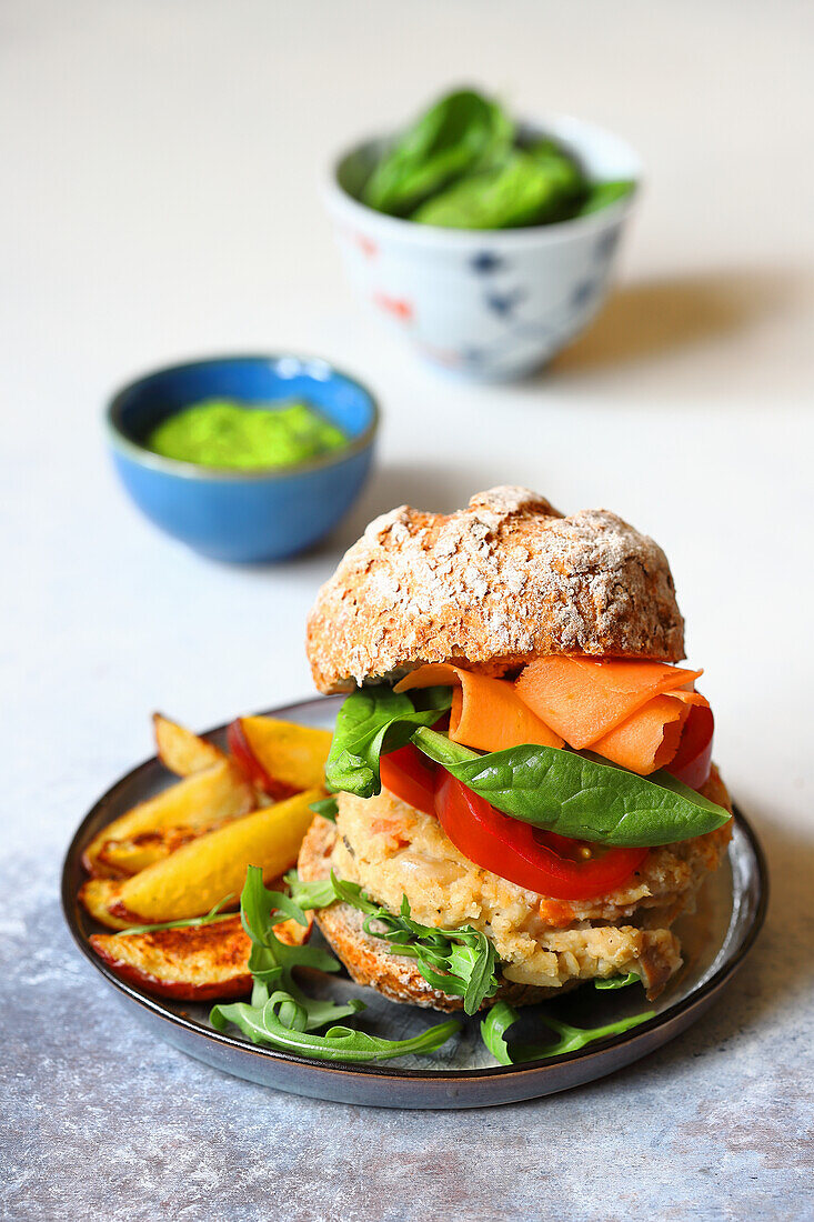 A bean burger with roasted potato wedges